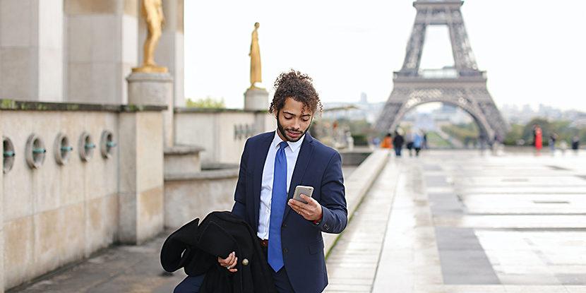 Businessman with smartphone near Eiffel Tower